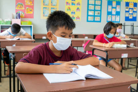 Elementary school wear mask for protect corona virus are studying at desks In Classroom,Health,Safety,Education,Back to school,Coronavirus school reopening concept.