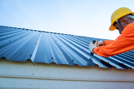 Roofer worker in protective uniform wear installing new roof,Concept of residential building under construction.