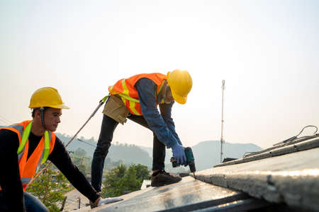 Construction worker wearing safety harness belt during working on roof structure of building on new roof. Stock fotó
