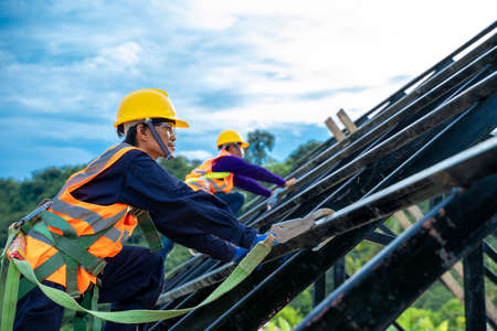 Engineer wearing safety harness and safety line working at high place at construction sites,Engineering tools and construction concept. Stock fotó