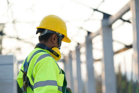 Engineer technician wearing safety harness and safety line working at construction site.