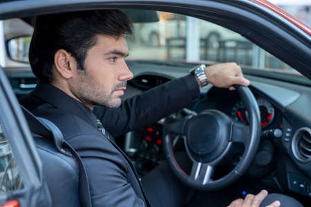 A confident handsome young businessman sitting in a sports car. Stock Photo