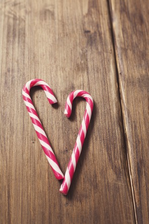 Heart in honor of Valentines day made from candy cane on a background of old wooden planks