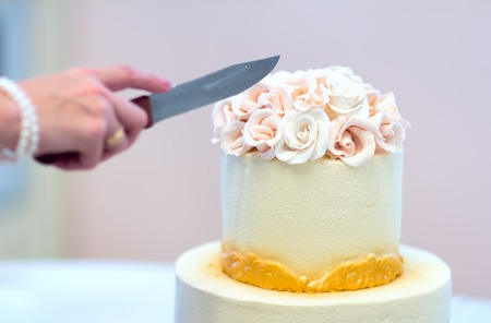Festive wedding cake with flowers, yellow-orange flowers, bunk, beautiful, gentle, the bride cuts the cake.