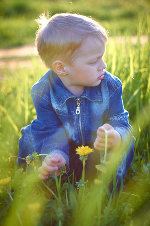 Little boy in cap playing outdoors in summer on a Sunny warm day, grass, greens, nature.