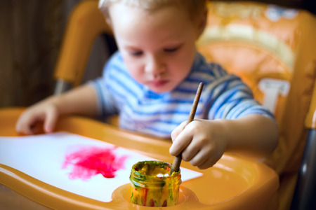 A little boy is sitting at the kids table, holding a brush, paint, paints. Stock Photo