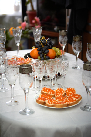 Festive wedding table, glasses of champagne, sandwiches with caviar, snacks, food, pineapples hearts love Stock Photo