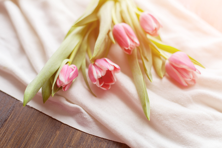 satin dress: Pink tulips on white fabric, lit by the rays of the setting sun