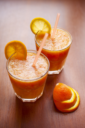 Lemon and orange smoothies on the table with slices of lemon and orange in a glass cups with tubes.