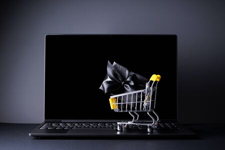 Black friday concept. A laptop with a yellow trolley with a black gift, on a black background.