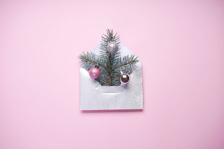 Christmas tree in the envelope, the minimum Christmas card, fir branch with colored Christmas balls on a pink background.