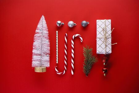 Christmas concept. Christmas gift, sweets, pine branch, toys on a red background. Flat lay. Stock Photo
