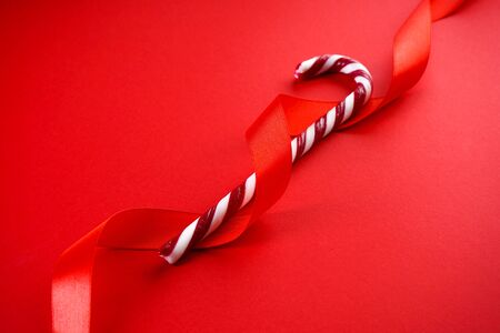 Christmas concept. Christmas candy cane with red ribbon on a red background. Close-up.