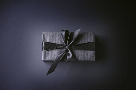 Black friday gift in black striped paper with a black ribbon, on a black background, top view Фото со стока