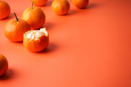 Plenty of fresh mandarin, a purified on an orange background with space for text.