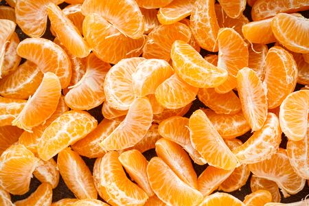 Flat lay slices of ripe tangerines on a dark background.
