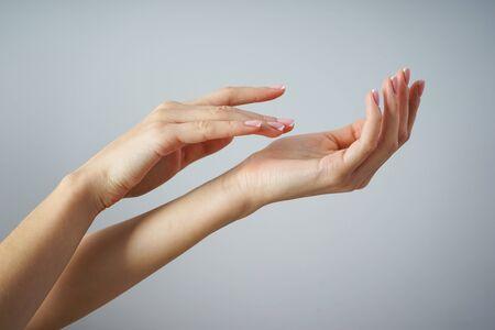 Schöne Hände eines jungen Mädchens mit schöner Maniküre auf grauem Hintergrund. Spa- und Maniküre-Konzept.