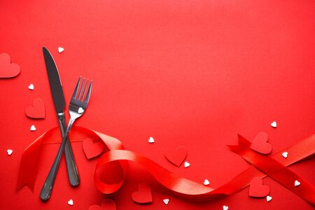 Valentine's Day. Love concept. Mothers Day. Hearts with cutlery and a red ribbon on a red background, with space for text, flat lay.