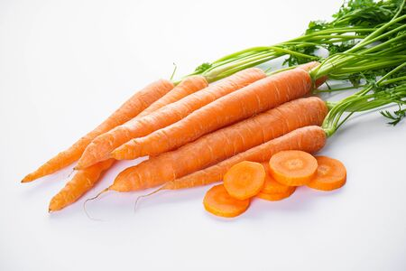 Fresh carrots with sliced and leaves on white background. Foto de archivo