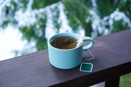 A cup of black tea on the railing of the terrace. Outside.