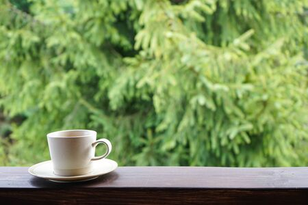 A cup of tea on the railing of the terrace. with place for text. Closeup. Foto de archivo