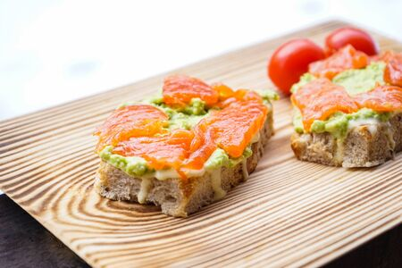 Sandwich with avocado, smoked salmon and tomatoes on a wooden board.