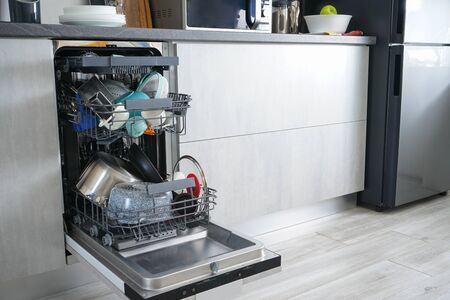 Dishwasher, open and loaded with dishes in the kitchen, after washing.