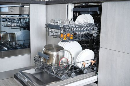 Clean dishes in the dishwasher in the kitchen, after washing.