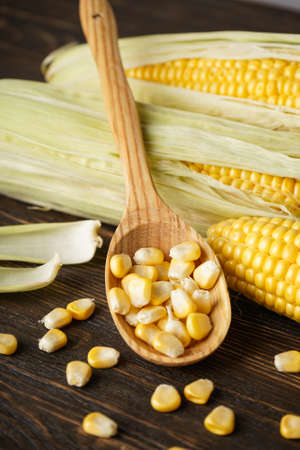 Cobs of ripe corn with grains of corn on a wooden background, vertical. Archivio Fotografico