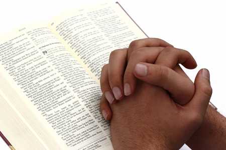 Praying hands on an open bible photo