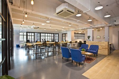this is photo of interior design with blue benches and wooden tables with gray floors with best quality and high resolution for you. Zdjęcie Seryjne