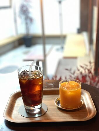 ice tea in a glass and orange ice in a glass on a tray Banco de Imagens