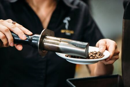 coffee beans are processed by coffee tools on a plate Banco de Imagens