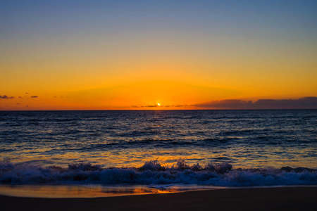 sunset orange in sea and sky blue beautiful sea and sunset with large yellow sun under the sea surface hills in the background.