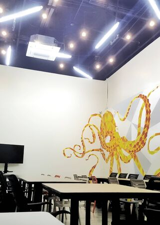 creative co working space office center with black chair,brown wood table,orange octopus wallpaper modern open space or shared workplace