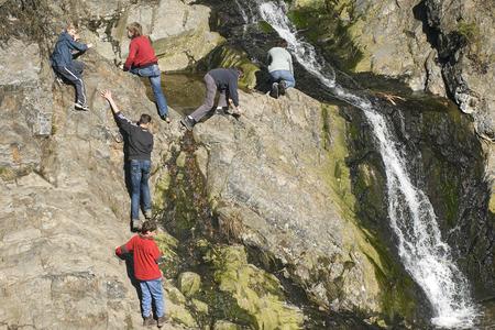 Kinderen klimmen naast een waterval in de Hoge Venen