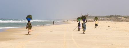 Woman walking while carrying baskets on the head on a Senegalese beach
