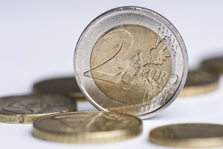 Used 2 euro coin standing between more coins