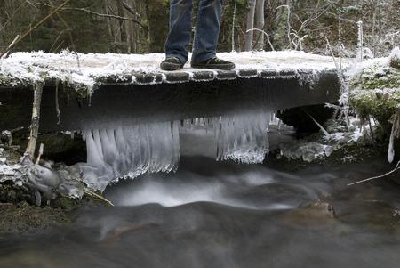 ijspegels die op een kleine brug hangen die een stroom in de Belgische Ardennen overschrijden Stockfoto