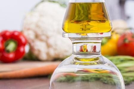 Olijfolie fles met vergroting van groenten op de achtergrond