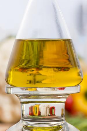 Olijfolie fles in de keuken met vergroting van groenten