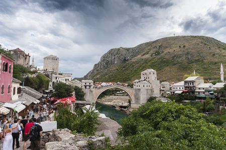 View on Stari Most old bridge in Mostar with the Neretva river and tourists walking in the small streets