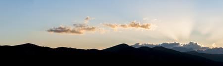 Landscape panorama of dark silhouette of hills after sunset with last sunlight behind the clouds
