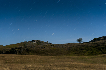 Nocuturnal moonlit landscape at Durmitor national park with startrails in the sky Stok Fotoğraf