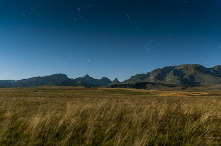 Nocuturnal moonlit landscape near Vrazje Jezero with Durmitor mountain in the background and startrails in the sky