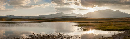 Best of sunset panorama over the beautiful Vrazje Jezero alsno named Devils lake in Montenegro with the landscape reflecting in the lake and the Durmitor mountain range in the background and the sun setting over it Stok Fotoğraf