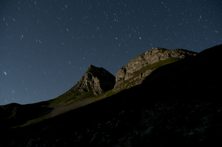 Nocturnal image of high peaks landscape in the Durmitor mountain range, lit by moonlight and with startrails and shadows of other peaks