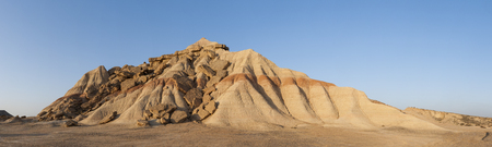 Eroded mountain hill panorama at Bardenas Reales with blue sky