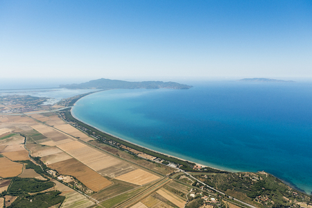 Aerial image showing the coastline of Italy with the Mediterranean Sea and the stretch of coast between Talamone Albinia and Fonteblanda with Monte Argentario peninsula in the background