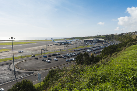 Aerial overview on João Paulo II Airport also named Aeroporto Ponta Delgada at Sao Miguel island in the Azores with airport parking lot and rental car parkings, main airport building  and planes on the airfield.  Stok Fotoğraf - 98497239